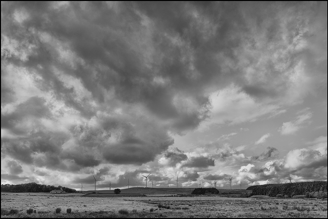 black and white photograph of a Northumberland UK landscape:two farms and wind turbines and sheep against a moody sky.