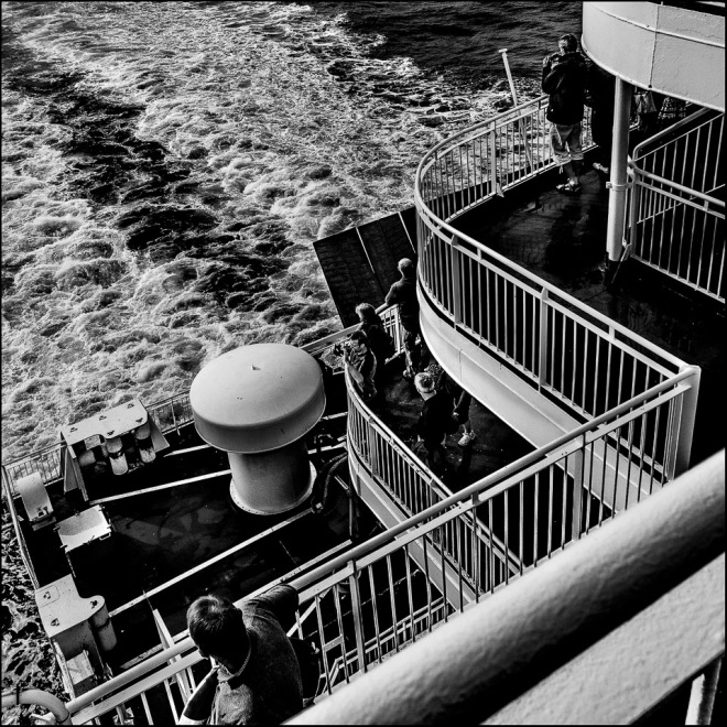 black and white photograph of people on the deck of a ferry