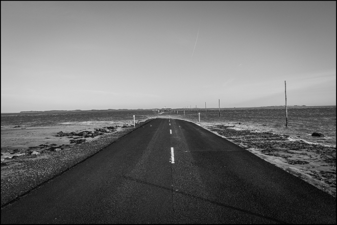 black and white photograph of the causeway to Holy Island being submerged as the tide comes in.